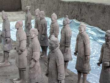 people in brown robe standing on brown sand during daytime - The terracotta figures were discovered in1974 in Xi'an, Shanxi province, China near the Mausole