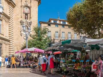 The main Flower Market in Aix-en-Provence in  Plce de Hotél de Ville - people walking on sidewalk near brown concrete building during daytime.