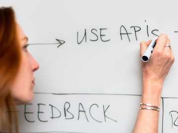 woman writing on white paper - Female software engineer uses whiteboard.