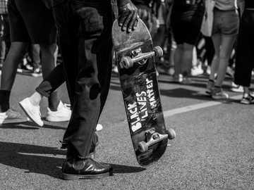 zdjęcie w skali szarości przedstawiające osobę trzymającą deskorolkę - Marsz Black Lives Matter w Lizbonie, Portugalia - 6 czerwca 2020 r. Lizbona, Portugalia