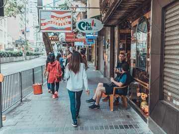 tylko podróż z żoną - kobieta chodzenie po chodniku w pobliżu kolei i sklepów. Hongkong
