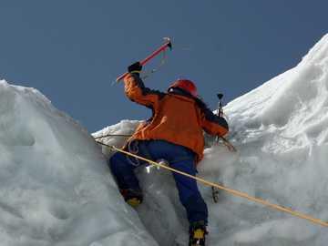 Алпинист на ледената стена - мъж в оранжево яке и сини панталони на заснежена плани�