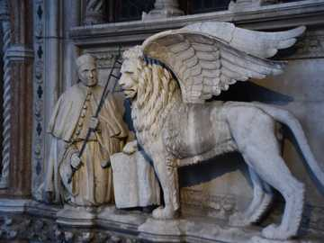 """priest and lion statue - On the top of the """"Door of the paper"""" in the Doge's Palace of Venice, you can see the"""