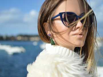 Faux Fur Fashion - woman wearing blue-framed cat-eye sunglasses with body of water background. Corfu, Greece