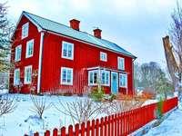 Casă roșie din lemn iarna în Suedia