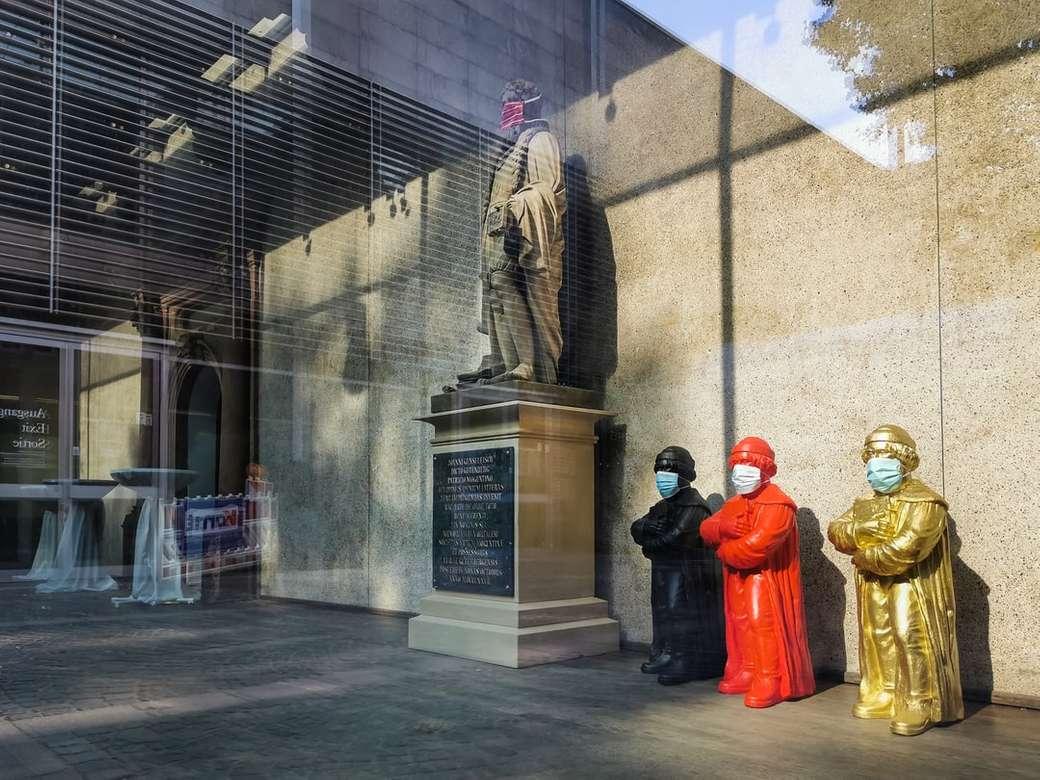 3 vörös köntöst viselő férfi szobor közelében nappal - Johannes Gutenberg szobra arcmaszkkal a Mainz Gutenberg Múzeumban. Gondolatok az ablakon keresztül. Gutenberg-Múzeum, Liebfrauenplatz, Mainz, Deutschland (2×2)