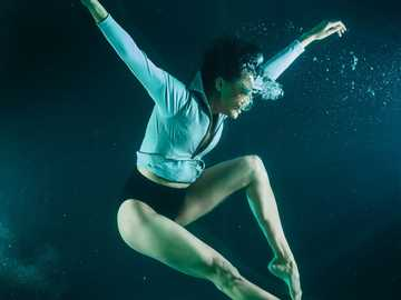 underwater fashion photography - woman in blue and white shirt and blue shorts in water. Turkey