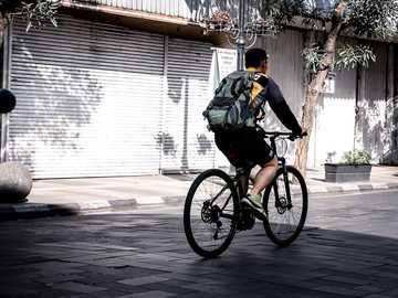 poranna jazda - mężczyzna jedzie na rowerze w pobliżu rolety. Braga, Bandung, Indonezja