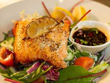 Fischgericht auf Teller - Im Ofen gebackenes Lachsfilet mit Chili-Soja-Sauce-Dressing, serviert auf einem gemischten Salat. Wi