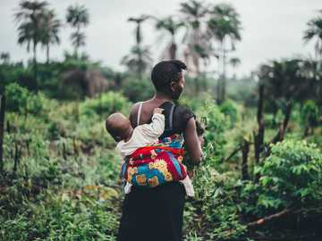 baby clinging on back - Tropical mother and child. Sierra Leone