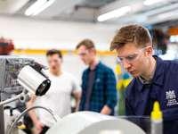 Ingegnere meccanico maschio costruisce robot agricoli - uomo in camicia a quadri blu e bianca con gli occhiali da vista.
