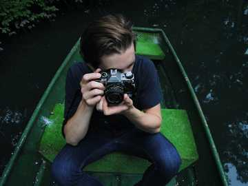 Photographer in a green boat - man in black t-shirt and blue denim jeans riding on row boat holding bridge camera on focus photo.