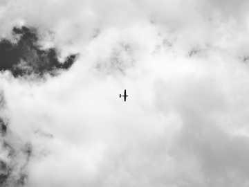 Small airplane over Jyväskylä - silhouette of airplane under white clouds.