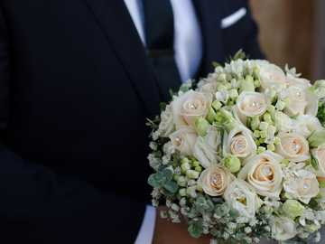 [gimme flowers and talk for hours] - man wearing black suit holding white rose bouquet.