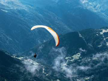 Voler dans les airs - personne en parapente sur les chaînes de montagnes.