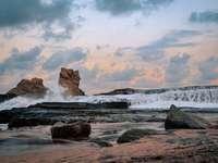 Sonnenuntergang am Klayar Beach, Ost-Java, Indonesien - braune Felsformation am Meeresufer während des Tages. Pantai Klayar, Jawa Timur, Indonesien