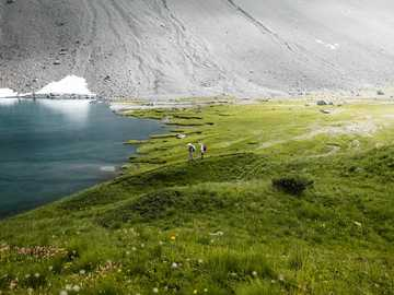 green grass field and body of water - Two hikers and a lake in the swiss mountains. Arosa, Schweiz