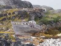 Заседнала в Гренландия лодка и стари къщи