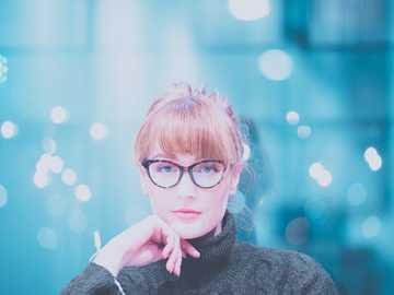 Bookish Bokeh - donna che indossa un maglione collo alto grigio che propone alla macchina fotografica. Melbourne, Au