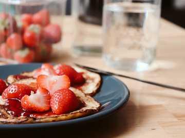 Fruchtiges Frühstück - Erdbeere und Blaubeere auf blauer Keramikplatte.