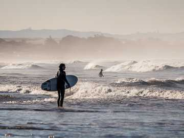 surf check - person holding white surfboard standing on body of water under gray sky during daytime. Pismo Beach,