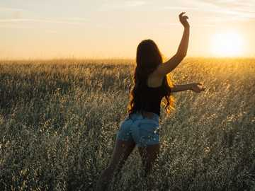 Dancing in the Sun - woman dancing at green grass field during sunset.