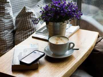 Kaffee, Blumen und Bücher - weißer Keramikbecher mit Latte Art.