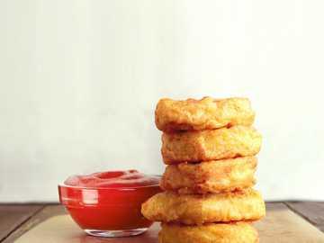 trzy ciasteczka na brązowej drewnianej desce do krojenia - Nuggetsy i Sos Pomidorowy.   phototastyfood.ru. Moskwa, Rosja