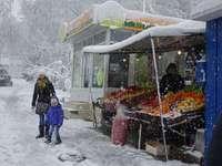 Град през зимата. - жена и дете се разхождат близо до магазина на заснежен�