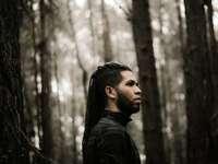 man die naast bomen staat - Jonge man in een bleek bos.