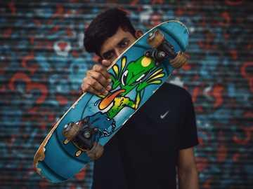 boys pose with skateboard - shallow focus photo of man holding blue skateboard. India
