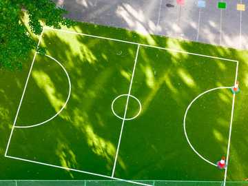 green and white soccer field - Green 5 a side football pitch dappled with sunlight on a playground. . London, UK