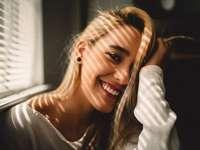 Luie zondag - selectieve aandacht fotografie van lachende vrouw met haar haren naast jaloezieën. Orlando, Verenig