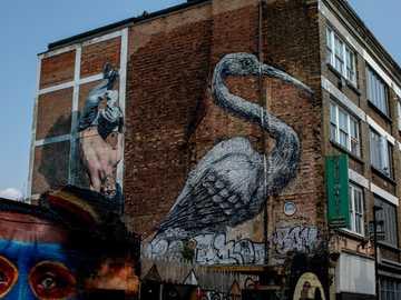 Brick Lane, Street Art, Graffiti. - braunes Backsteingebäude mit grauer Vogelmalerei.
