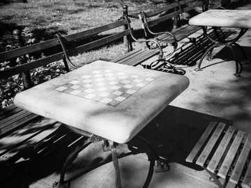 Chess tables in a city park. - grayscale photo of wooden table. New York, NY, USA