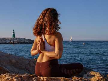 Free your Mind  TLV Dec 2019 @morshanik - woman sitting while doing yoga on rock viewing body of water during daytime. Tel Aviv Port