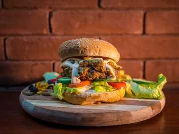 Burger juteux - pain avec galette et hamburger de tomates et de laitue en tranches.