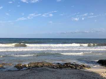 Vie de plage - rivage rocheux brun sous un ciel bleu pendant la journée. Cala Millor, Cala Millor, Espagne