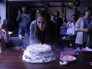 Éruption d'anniversaire - femme soufflant des bougies sur le gâteau.