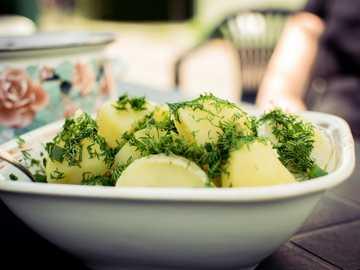 Tranches de concombre sur bol en céramique blanche - Un tas de pommes de terre bouillies avec de l'aneth dessus le matin d'été. Zapyškis, Di