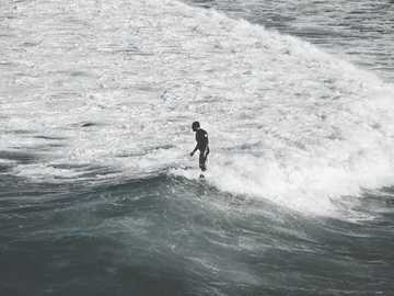 man standing on sea shore with waves - I spend more than 15 min watching people surfing at Maroubra Beach in Sydney. I wonder if they ever