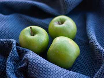 Pomme verte, fruits sur une table - pomme verte sur textile à carreaux noir et blanc.