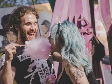 Cotton Candy - man and woman laughing while eating cotton candy.