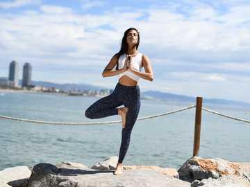 woman stands and poses near shore - Gilr doing yoga at Barcelona beach #cbdoil #breatheorganics #sport .