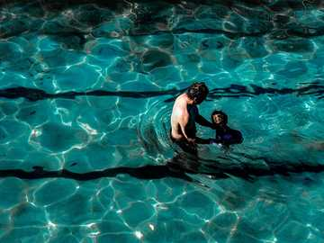 Father and Son - man in blue shorts swimming in water. Clovelly, Clovelly, Australia