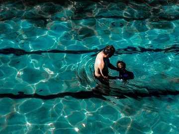 Père et fils - homme en short bleu nageant dans l'eau. Clovelly, Clovelly, Australie