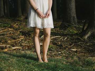 pessoa em pé ao lado das árvores - Mulher em um vestido por uma floresta.