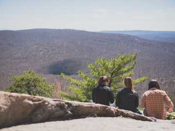 The Cliff - women sits on ground near green trees. Bear Mountain State Park, Tomkins Cove, United States