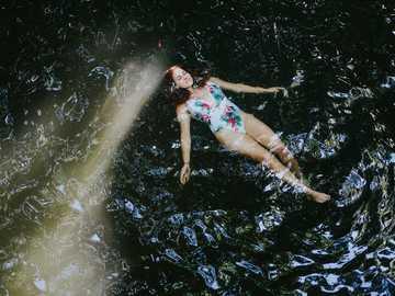 Femme en bikini floral bleu et blanc allongé sur l'eau - À la poursuite des chutes d'eau avec HaveFunDoGood.co au Costa Rica. Costa Rica