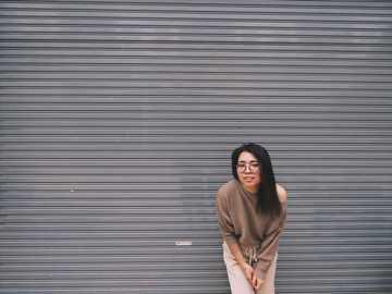 woman leaning on gray garage door - Ok, aku sedang berjalan disekitar lingkungan baru dan menemukan dinding bergaris ini.